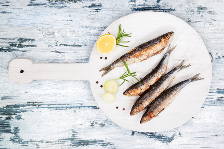 Delicious grilled sardines on wooden kitchen board on white and blue wooden textured background. Culinary seafood eating. photo