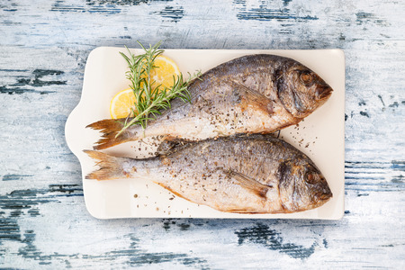 sea bream: Delicious grilled sea bream fish on kitchen board with rosemary, lemon and colorful peppercorns on white textured wooden background. Culinary healthy cooking. Stock photo. Stock Photo