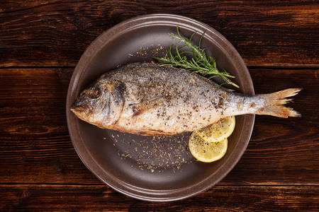 gilthead: Grilled fish on brown plate with herbs and lemon on old wooden background, top view. Mediterranean luxurious seafood concept. Stock Photo