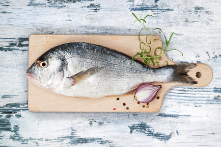 bream: Delicious fresh sea bream fish on wooden kitchen board with onion, rosemary and colorful peppercorns on white and blue textured wooden background. Culinary healthy cooking.