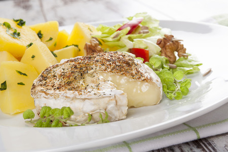 country style: Melted camembert cheese with cooked potatoes and fresh mixed salad. Culinary vegetarian eating, country style. Stock Photo