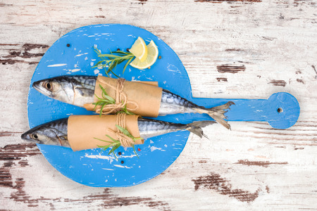 Delicious fresh mackerel fish on wooden kitchen board with fresh herbs and lemon on white textured wooden background. Culinary healthy cooking. photo