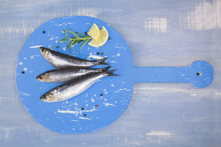 anchovy fish: Three fresh anchovy fish on round blue wooden kitchen board on blue wooden table, top view. Culinary seafood concept. Delicious healthy eating.