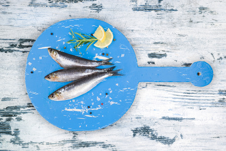anchovy fish: Three fresh anchovy fish on round blue wooden kitchen board on white and blue wooden table, top view. Culinary seafood concept. Delicious healthy eating.