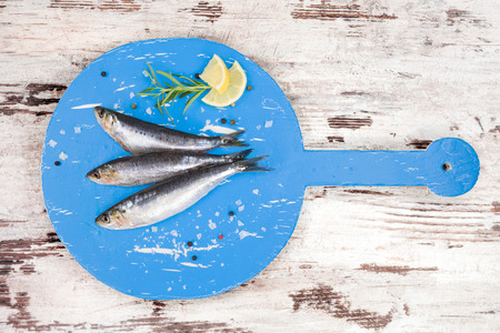 anchovy fish: Three fresh anchovy fish on round blue wooden kitchen board on white and brown wooden table, top view. Culinary seafood concept. Delicious healthy eating.