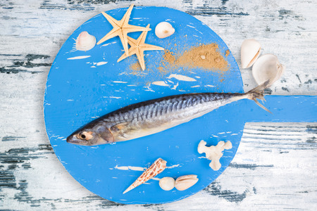 Delicious fresh fish on wooden kitchen board with sea shells on white textured wooden background. Culinary healthy cooking. photo