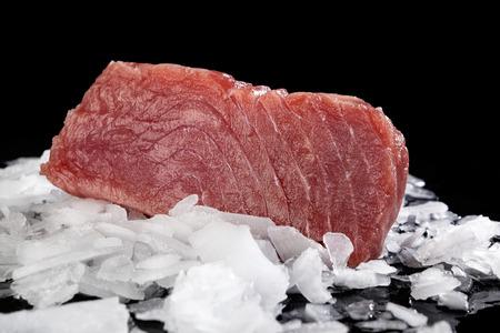 ice crushed: Verse grote tonijnsteak op gemalen ijs geïsoleerd op een zwarte achtergrond. Sashimi sushi, vis eten, gezond voedsel.