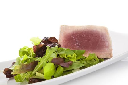 culinair: Tonijnsteak met salade op een witte achtergrond. Culinair seafood eten. Stockfoto