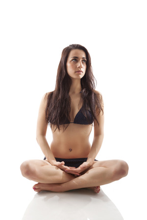 kneeling woman: Meditation practice. Sexy smiling young woman in lotus position meditating isolated on white background. Balance and piece.