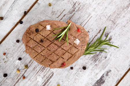 country style: Luxurious tenderloin steak with herbs and peppercorn on white vintage wooden background, top view. Steak eating, country style. Stock Photo