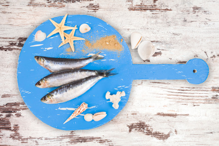 anchovy fish: Three fresh anchovy fish on blue wooden kitchen board on brown and white wooden table, top view. Culinary seafood concept. Delicious healthy eating.