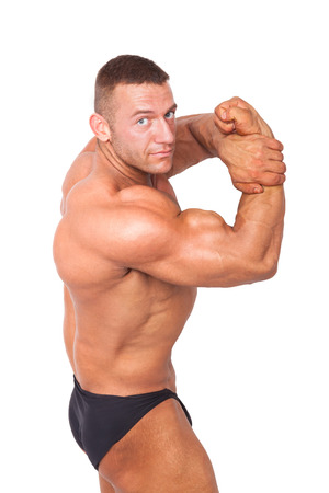 Bodybuilder posing. Huge muscular bodybuilder showing biceps isolated on white background. Sports and fitness.