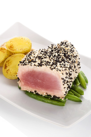 white sesame seeds: Grilled tuna steak wrapped in black and white sesame seeds on green beans with potatoes on white plate on white background. Culinary seafood eating.