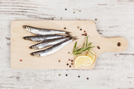 gezond koken: Delicious fresh sardines on wooden kitchen board with lemon, rosemary and colorful peppercorns on wooden background. Culinary healthy cooking. Stockfoto