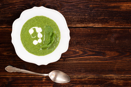 Spinach cream soup in rustic plate on wooden background, top view with copy space. Culinary soup eating.