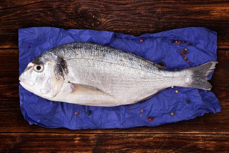 sea bream: Delicious fresh sea bream fish on blue napkin with colorful peppercorns