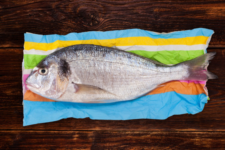 gilt head: Fresh sea bream fish on colorful napkin on vintage wooden table. Culinary seafood eating. Stock Photo