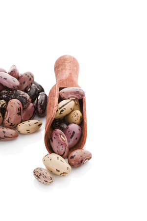 pinto beans: Pinto beans on wooden scoop isolated on white background. Healthy legume eating.