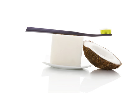 Hard organic coconut oil with toothbrush and coconut isolated on white background. Natural organic dental hygiene. Stockfoto