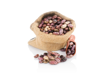 pinto bean: Pinto beans in burlap bag with wooden scoop isolated on white background. Healthy legume eating.