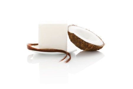 Organic hard coconut oil with a string of hair and half coconut isolated on white background. Natural organic cosmetics, body and hair care. photo