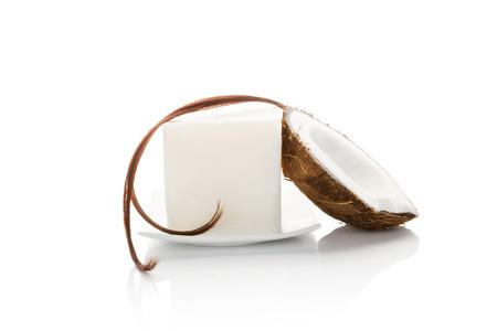 aceite de coco: El aceite de coco org�nico duro con una cadena de cabello y medio coco aislado en el fondo blanco. Cosm�ticos org�nicos naturales, el cuerpo y el cuidado del cabello.