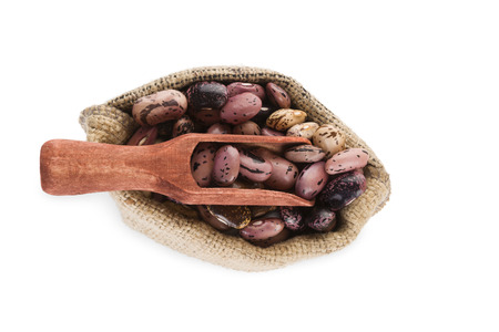 Pinto beans in burlap bag with wooden scoop isolated on white background, top view. Healthy legume eating. photo