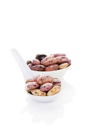 culinary arts: Pinto beans on white spoon isolated on white background. Healthy legume eating. Fresh modern image language. Culinary arts.