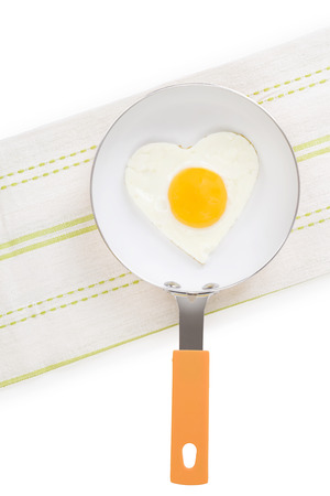 sunnyside: Fried egg in heart shape on pan isolated on white background, top view. Fresh modern image language. Culinary arts. Stock Photo