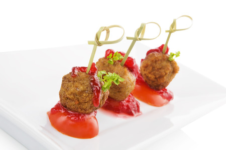 culinary arts: Delicious meatballs canape isolated on white background. Fresh modern image language. Culinary arts. Stock Photo