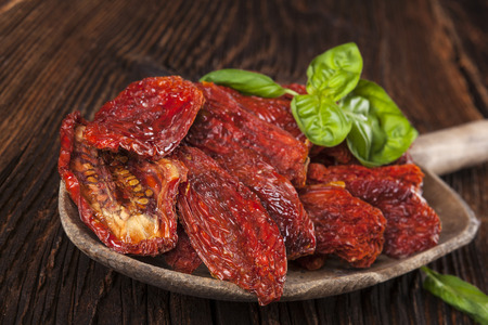culinary: Sundried tomatoes and fresh basil leaves on brown wooden background. Culinary italian eating.
