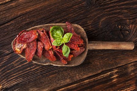 tomato: Sundried tomatoes and fresh basil leaves on brown wooden background. Culinary italian eating.