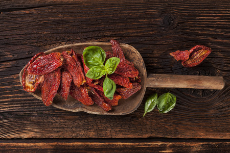 sundried: Sundried tomatoes and fresh basil leaves on brown wooden background. Culinary italian eating.