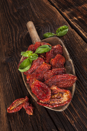 culinair: Zongedroogde tomaten en verse basilicum bladeren op bruine houten achtergrond. Culinaire Italiaans eten.