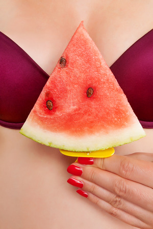 Sexy ice cream eating. Sexy hot woman with red fingernails holding red water melon ice cream between her breast. Sexy summer ice cream eating. Sexy summer. photo