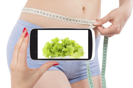 weightloss: Weightloss and diet in information age. Diet, detox and fitness app on smartphone screen and attractive beautiful woman measuring her body with tape measure. Modern technology and healthy lifestyle.