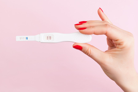Beautiful female hand with red fingernails holding positive pregnancy test isolated on pink background. Motherhood, pregnancy, birth control concept. Minimal sparse modern image language.