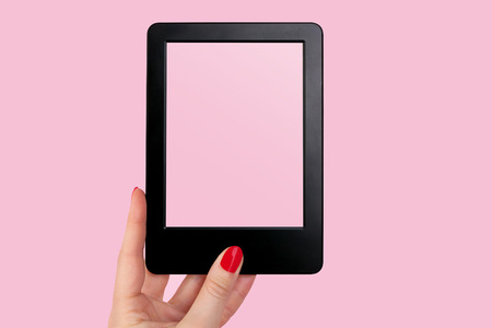 e reader: Female hand with red nails holding e reader against pink background. Modern book reading.