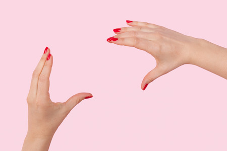 nonverbal communication: Female hands with red fingernails doing photography gesture against pink background. Nonverbal communication, vision and photography. Stock Photo
