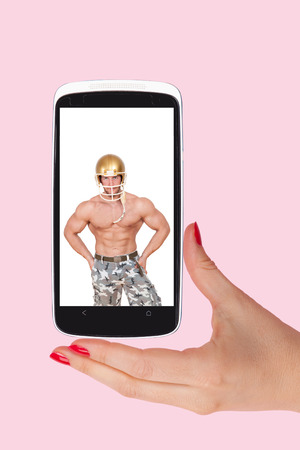 information age: Online dating. Female hands holding smartphone with picture of handsome man isolated on pink background. Flirting and relationship in the information age. Stock Photo