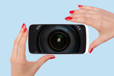sexy photo: Selfie. Female hands with red nails holding smartphone with optical lens on screen. Modern social media picture communication. Stock Photo