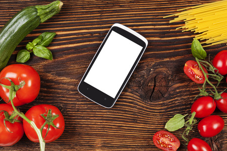 information age: Fresh vegetables and pasta on wooden table with smartphone and recipe on screen. Groceries, recipe and cooking. Modern food preparation.