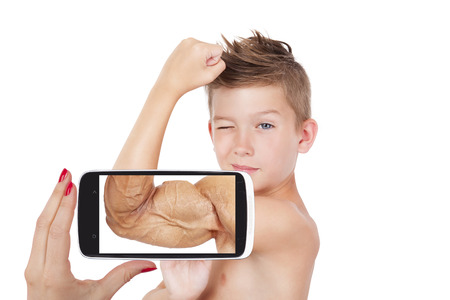 self conscious: Vision of success. Charming boy showing muscle with future vision on smartphone screen. Seeing the future, self confidence and self perception. Stock Photo