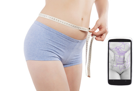 weightloss: Beautiful caucasian girl measuring her waist with tape measure isolated on white background and weightloss and fitness app on spartphone screen. Healthy living in the information age.