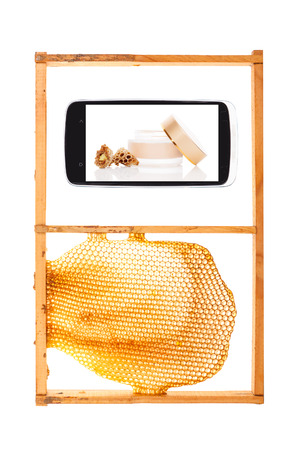information age: All information on your fingertips. Honeycomb and smartphone with royal jelly cosmetics. Information age concept.