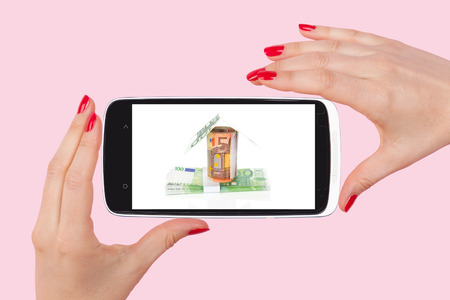 fingertips: Mortgage at your fingertips. Female hand holding a smartphone with house made from bills isolated on pink background. Stock Photo