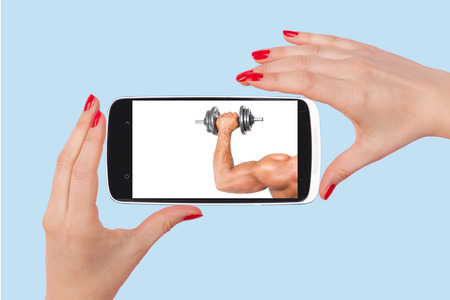 Online dating. Female hands holding smartphone with picture of handsome man isolated on pink background. Flirting and relationship in the information age. photo
