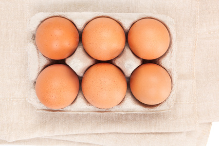 Natural organic chicken eggs in cardboard package, top view. Natural healthy eating.