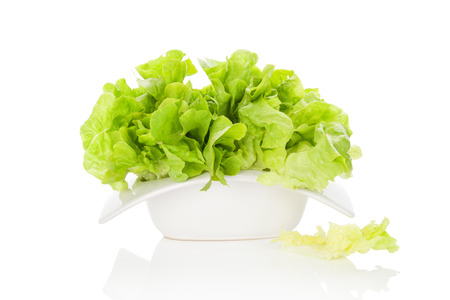 culinary arts: Fresh green salad in white bowl isolated on white background. Fresh healthy summer eating. Culinary arts. Stock Photo