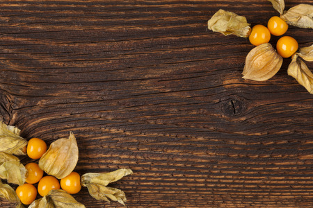 husk tomato: Physalis background with copyspace. Ground cherry on wooden rustic table top view. Healthy fresh fruit eating.
